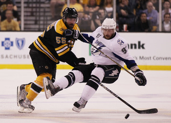 BOSTON, MA - MAY 27:  Johnny Boychuk #55 of the Boston Bruins knocks Steven Stamkos #91 of the Tampa Bay Lightning to the ice in the first period of Game Seven of the Eastern Conference Finals during the 2011 NHL Stanley Cup Playoffs at TD Garden on May 2