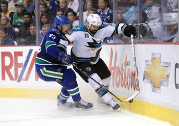 VANCOUVER, CANADA - MAY 24:  Jamal Mayers #10 of the San Jose Sharks moves the puck along the end boards against the San Jose Sharks Alexander Edler #23 of the Vancouver Canucks defends the play in Game Five of the Western Conference Finals during the 201