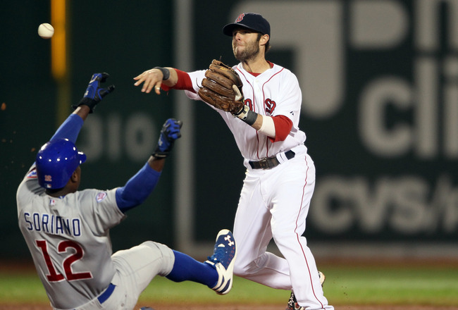 BOSTON, MA - MAY 22:  Dustin Pedroia #15 of the Boston Red Sox turns the double play as Alfonso Soriano #12 of the Chicago Cubs is out at second in the third inning on May 22, 2011 at Fenway Park in Boston, Massachusetts.  Before this series, the two team