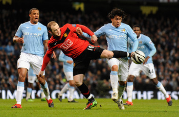 MANCHESTER, UNITED KINGDOM - JANUARY 19:   Wayne Rooney of Manchester United battles for the ball with Carlos Tevez of Manchester City during the Carling Cup Semi Final match between Manchester City and Manchester United at the City of Manchester Stadium