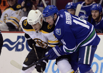 VANCOUVER, CANADA - FEBRUARY 26: Alexandre Burrows #14 of the Vancouver Canucks gets in close to Milan Lucic #17 of the Boston Bruins on a face-off during the third period in NHL action on February 26, 2011 at Rogers Arena in Vancouver, British Columbia,