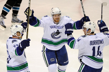 SAN JOSE, CA - MAY 20:  Henrik Sedin #33, Daniel Sedin #22 and Alex Burrows #14 of the Vancouver Canucks celebrate Burrow's third period goal in Game Three of the Western Conference Finals against the San Jose Sharks during the 2011 Stanley Cup Playoffs a