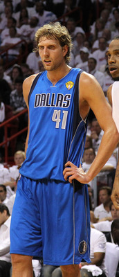 Dirk Nowitzki stands along the side of the paint as his teammate takes a free throw.