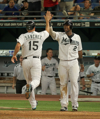 MIAMI GARDENS, FL - MAY 18:  Gaby Sanchez #15 and Hanley Ramirez #2 of the Florida Marlins high-five after Sanchez scored during a game against the Chicago Cubs at Sun Life Stadium on May 18, 2011 in Miami Gardens, Florida.  (Photo by Mike Ehrmann/Getty I