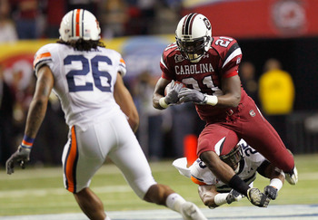 ATLANTA, GA - DECEMBER 04:  Marcus Lattimore #21 of the South Carolina Gamecocks is tackled by Daren Bates #25 of the Auburn Tigers during the 2010 SEC Championship at Georgia Dome on December 4, 2010 in Atlanta, Georgia.  (Photo by Kevin C. Cox/Getty Ima
