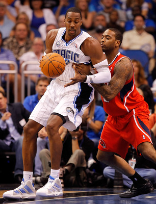 ORLANDO, FL - APRIL 16:  Dwight Howard #12 of the Orlando Magic drives on Jason Collins #34 of the Atlanta Hawks during Game One of the Eastern Conference Quarterfinals of the 2011 NBA Playoffs on April 16, 2011 at the Amway Arena in Orlando, Florida.  NO