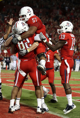 TUCSON, AZ - SEPTEMBER 25:  Jovon Hayes #57 of the Arizona Wildcats jumps into the arms of wide receiver Juron Criner #82 after Criner caught the game winning 3 yard touchdown reception against the California Bears during the fourth quarter of the college