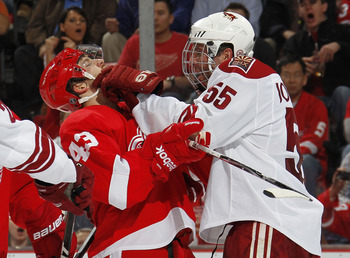 DETROIT, MI - APRIL 16:  Ed Jovanovski #55 of the Phoenix Coyotes puts a glove in the face of Darren Helm #43 of the Detroit Red Wings in Game Two of the Western Conference Quarterfinals during the 2011 Stanley Cup Playoffs at Joe Louis Arena on April 16,
