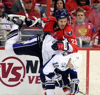 WASHINGTON, DC - APRIL 29:  Scott Hannan #23 of the Washington Capitals collides with Sean Bergenheim #10 of the Tampa Bay Lightning during Game One of the Eastern Conference Semifinal during the 2011 NHL Stanley Cup Finals at the Verizon Center on April