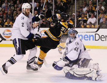 BOSTON, MA - MAY 23:  Eric Brewer #2 of the Tampa Bay Lightning checks Patrice Bergeron #37 of the Boston Bruins as Mike Smith #41 of the Tampa Bay Lightning looks on in Game Five of the Eastern Conference Finals during the 2011 NHL Stanley Cup Playoffs a