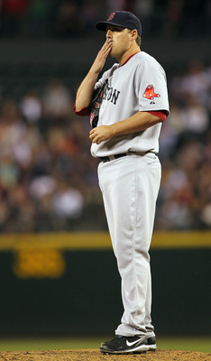SEATTLE - JULY 22:  Starting pitcher John Lackey #40 of the Boston Red Sox reacts after yielding a base hit to Josh Bard #26 of the Seattle Mariners at Safeco Field on July 22, 2010 in Seattle, Washington. The hit broke up a no-hitter in the eighth inning