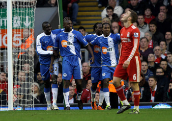 LIVERPOOL, ENGLAND - FEBRUARY 12:  Steve Gohouri of Wigan Athletic celebrates scoring his team's first goal with his team mates during the Barclays Premier League match between Liverpool and Wigan Athletic at Anfield on February 12, 2011 in Liverpool, Eng