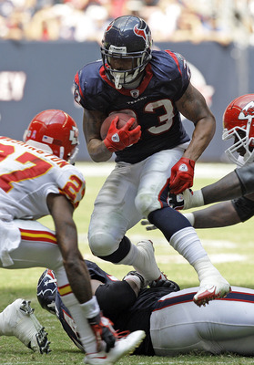 HOUSTON - OCTOBER 17:  Running back Adrian Foster #23 of the Houston Texans looks for room to run as cornerback Donald Washington #27 and  Glenn Dorsey #72 of the Kasnsas City Chiefs at Reliant Stadium on October 17, 2010 in Houston, Texas.  (Photo by Bob