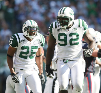 EAST RUTHERFORD, NJ - SEPTEMBER 20: Shaun Ellis #92 of the New York Jets celebrates a play in front of teammate Kerry Rhodes #25 against the New England Patriots at Giants Stadium on September 20, 2009 in East Rutherford, New Jersey.  (Photo by Nick Laham