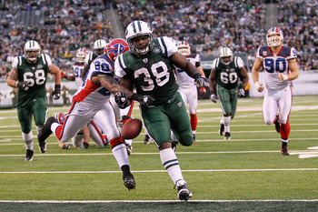 EAST RUTHERFORD, NJ - JANUARY 02:  John Conner #38 of the New York Jets looses the ball after scoring a touchdown against the defense of Donte Whitner #20 of the Buffalo Bills at New Meadowlands Stadium on January 2, 2011 in East Rutherford, New Jersey.
