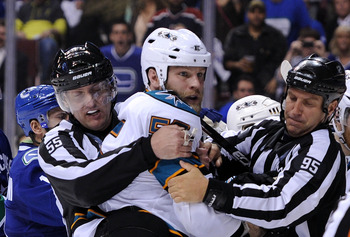 VANCOUVER, BC - MAY 18:  NHL Linesmen Shane Heyer #55 and Jonny Murray #95 hold back Ben Eager #55 of the San Jose Sharks as Eager gets called for an unsportsmanlike conduct penalty for standing over goaltender Roberto Luongo #1 of the Vancouver Canucks a