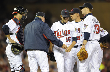 MINNEAPOLIS, MN - APRIL 9: Manager Ron Gardenhire #35 of the Minnesota Twins takes the ball from relief pitcher Glen Perkins #15 as Joe Mauer #7 (L), Danny Valencia #19 and Justin Morneau #33 look on during the seventh inning of their game against the Oak