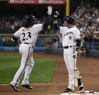 MILWAUKEE, WI - APRIL 04: Rickie Weeks #23 of the Milwaukee Brewers is congratulated by teammate Ryan Braun #8 after hitting a solo home run in the 3rd inning against the Atlanta Braves during the home opener at Miller Park on April 4, 2011 in Milwaukee,
