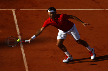 PARIS, FRANCE - MAY 31:  Roger Federer of Switzerland sits a forehand during the men's singles quarterfinal match between Gael Monfils of France and Roger Federer of Switzerland on day ten of the French Open at Roland Garros on May 31, 2011 in Paris, Fran