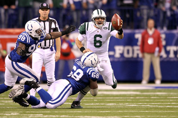 INDIANAPOLIS, IN - JANUARY 08:  Quarterback Mark Sanchez #6 of the New York Jets attempts to escape the pressure by Eric Foster #68 and Robert Mathis #98 of the Indianapolis Colts during their 2011 AFC wild card playoff game at Lucas Oil Stadium on Januar