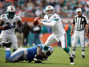 MIAMI - DECEMBER 26:  Quarterback Chad Henne #7 of the Miami Dolphins is preasured by Lawrence Jackson #94 of the Detroit Lions at Sun Life Stadium on December 26, 2010 in Miami, Florida.  (Photo by Marc Serota/Getty Images)