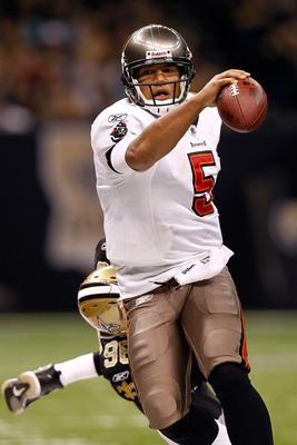 NEW ORLEANS, LA - JANUARY 02:  Quarterback Josh Freeman #5 of the Tampa Bay Buccaneers is pushed out of bounds by Alex Brown #96 of the New Orleans Saints at the Louisiana Superdome on January 2, 2011 in New Orleans, Louisiana.  The Buccaneers defeated th