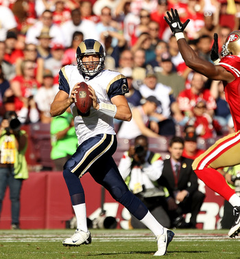 SAN FRANCISCO - NOVEMBER 14:  Sam Bradford #8  of the St. Louis Rams is chased by Manny Lawson #99 of the San Francisco 49ers at Candlestick Park on November 14, 2010 in San Francisco, California.  (Photo by Ezra Shaw/Getty Images)