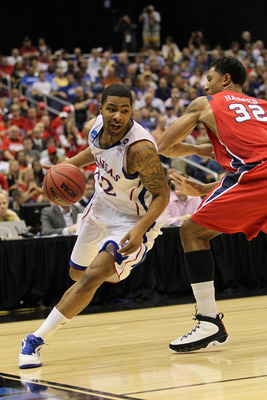 SAN ANTONIO, TX - MARCH 25:  Marcus Morris #22 of the Kansas Jayhawks drives against Justin Harper #32 of the Richmond Spiders during the southwest regional of the 2011 NCAA men's basketball tournament at the Alamodome on March 25, 2011 in San Antonio, Te