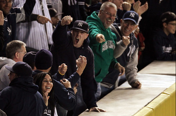 NEW YORK - OCTOBER 19:  Fans react after catching a home run ball hit by Robinson Cano #24 of the New York Yankees in the bottom of the second inning of Game Four of the ALCS during the 2010 MLB Playoffs at Yankee Stadium on October 19, 2010 in the Bronx