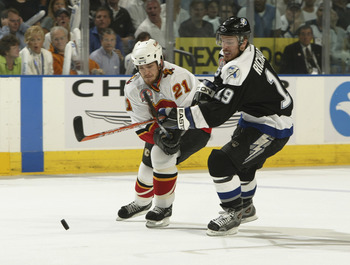 TAMPA, FL - JUNE 7:  Andrew Ference #21 of the Calgary Flames skates for the puck against Brad Richards #19 of the Tampa Bay Lightning in Game seven of the NHL Stanley Cup Finals on June 7, 2004 at the St. Pete Times Forum in Tampa, Florida. The Lightning