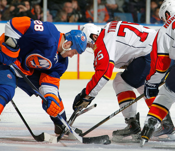 UNIONDALE, NY - FEBRUARY 21: Scott Timmins #75 of the Florida Panthers and Zenon Konopka #28 of the New York Islanders face off during an NHL hockey game at the Nassau Coliseum on February 21, 2011 in Uniondale, New York.  (Photo by Paul Bereswill/Getty I