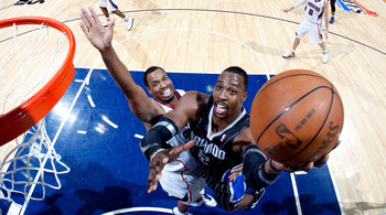 ATLANTA, GA - APRIL 24:  Dwight Howard #12 of the Orlando Magic attacks the basket against Jason Collins #34 of the Atlanta Hawks during Game Four of the Eastern Conference Quarterfinals in the 2011 NBA Playoffs at Philips Arena on April 24, 2011 in Atlan