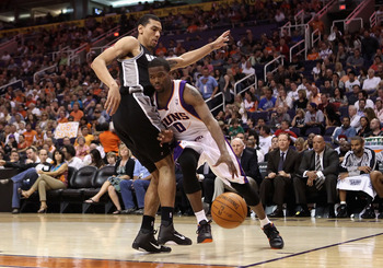 PHOENIX, AZ - APRIL 13:  Aaron Brooks #0 of the Phoenix Suns drives the ball against George Hill #4 of the San Antonio Spurs during the NBA game at US Airways Center on April 13, 2011 in Phoenix, Arizona.  NOTE TO USER: User expressly acknowledges and agr