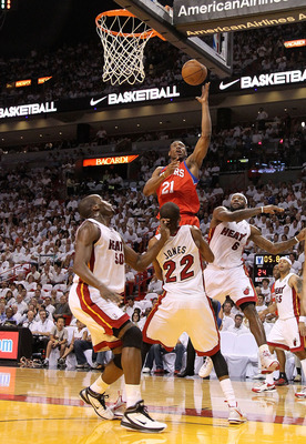 MIAMI, FL - APRIL 27: Thaddeus Young #21 of the Philadelphia 76ers shoots over James Jones #22 and Joel Anthony #50 of the Miami Heat during game five of the Eastern Conference Quarterfinals in the 2011 NBA Playoffs at American Airlines Arena on April 27,