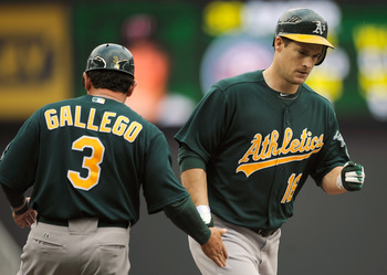 MINNEAPOLIS, MN - APRIL 10: Third base coach Mike Gallegro #3 of the Oakland Athletics congratulates Josh Willingham #16 as he rounds the bases following a solo home run off of Scott Baker #30 of the Minnesota Twins during the fourth inning of their game