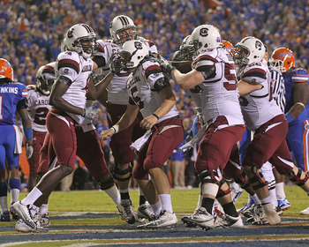 GAINESVILLE, FL - NOVEMBER 13:  Stephen Garcia #5 of the South Carolina Gamecocks is congratulated by teammates after rushing for a touchdown during a game against the Florida Gators at Ben Hill Griffin Stadium on November 13, 2010 in Gainesville, Florida