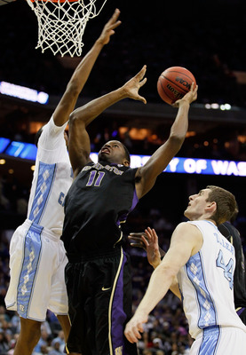 CHARLOTTE, NC - MARCH 20:  Matthew Bryan-Amaning #11 of the Washington Huskies goes up for a shot between John Henson #31 and Tyler Zeller #44 of the North Carolina Tar Heels in the first half during the third round of the 2011 NCAA men's basketball tourn