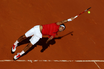 PARIS, FRANCE - MAY 31:  Roger Federer of Switzerland serves during the men's singles quarterfinal match between Gael Monfils of France and Roger Federer of Switzerland on day ten of the French Open at Roland Garros on May 31, 2011 in Paris, France.  (Pho
