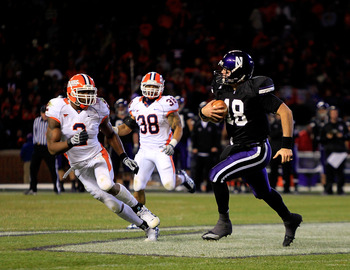 CHICAGO - NOVEMBER 20: Evan Watkins #18 of the Northwestern Wildcats runs for a first down pursued by Travon Wilson #3 and Ian Thomas #38 of the Illinois Fighting Illini during a game played at Wrigley Field on November 20, 2010 in Chicago, Illinois. Illi