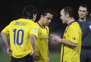 ALMERIA, SPAIN - MARCH 06:  Lionel Messi, Xavi Hernandez and Andres Iniesta (R) of Barcelona talk before Messi scored from a free kick during the La Liga match between UD Almeria and Barcelona at Estadio del Mediterraneo on March 6, 2010 in Almeria, Spain
