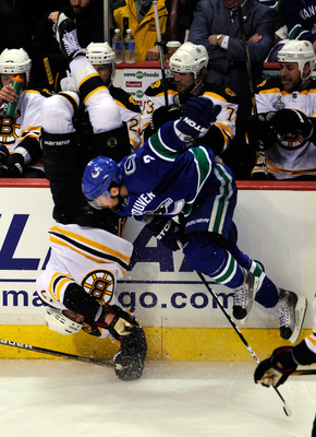 VANCOUVER, BC - JUNE 01:  Milan Lucic #17 of the Boston Bruins gets flipped after being check by Dan Hamhuis #2 of the Vancouver Canucks during game one of the 2011 NHL Stanley Cup Finals at Rogers Arena on June 1, 2011 in Vancouver, Canada.  (Photo by Ri
