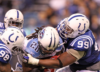 INDIANAPOLIS - JANUARY 02:  Chris Johnson #28 of the Tennessee Titans is tackled by Robert Mathis #98 and Antonio Johnson #99 of the Indianapolis Colts at Lucas Oil Stadium on January 2, 2011 in Indianapolis, Indiana.  the Colts won 23-20.  (Photo by Andy