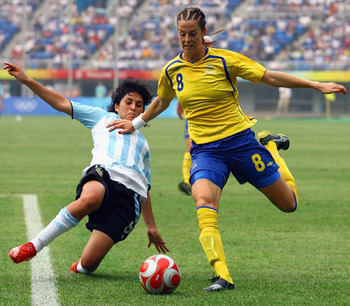 TIANJIN, CHINA - AUGUST 09:  Gabriela Chavez of Argentina challenges Lotta Schelin of Sweden during the Women's Group E match between Sweden and Argentina on Day 1 of the Beijing 2008 Olympic Games on August 9, 2008 in Tianjin, China.  (Photo by Koji Wata