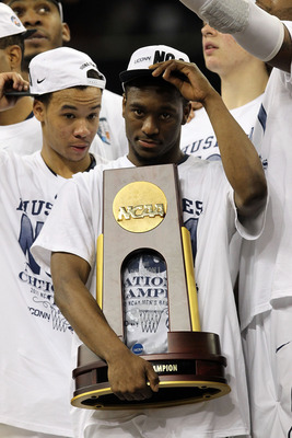 HOUSTON, TX - APRIL 04:  Kemba Walker #15 of the Connecticut Huskies holds the trophy as he and his team celebrate after defeating the Butler Bulldogs to win the National Championship Game of the 2011 NCAA Division I Men's Basketball Tournament by a score