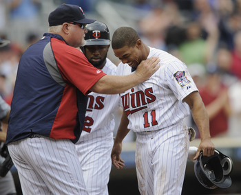 MINNEAPOLIS, MN - MAY 11: Manager Ron Gardenhire #35 of the Minnesota Twins checks on Ben Revere #11 of the Minnesota Twins after a hard slide into home plate by Revere against the Detroit Tigers during in the eighth inning of their game on May 11, 2011 a