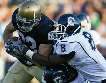 SOUTH BEND, IN - NOVEMBER 21: Robby Parris #82 of the Notre Dame Fighting Irish is brought down by Robert Vaughn #33 and Lawrence Wilson #8 of the Univeristy of Connecticut Huskies at Notre Dame Stadium on November 21, 2009 in South Bend, Indiana. Connect