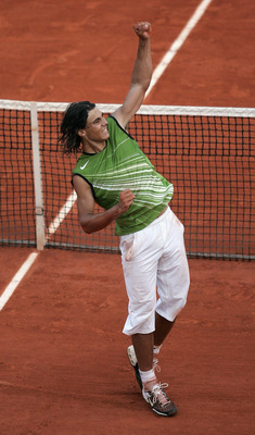PARIS - JUNE 3:  Rafael Nadal of Spain celebrates match point as he defeats Roger Federer of Switzerland in four sets during their semi-final match on the twelfth day of the French Open at Roland Garros on June 3, 2005 in Paris, France.  (Photo by Clive M