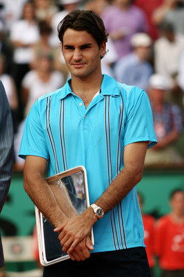 PARIS - JUNE 10:  Roger Federer of Switzerland holds the runners up trophy after losing to Rafael Nadal of Spain in the Men's Singles Final on day fifteen of the French Open at Roland Garros on June 10, 2007 in Paris, France.  (Photo by Clive Brunskill/Ge