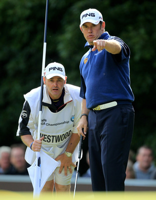 VIRGINIA WATER, ENGLAND - MAY 29:  Lee Westwood of England and Caddy Billy Foster line up a putt during the final round of the BMW PGA Championship  at the Wentworth Club on May 29, 2011 in Virginia Water, England.  (Photo by David Cannon/Getty Images)