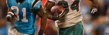 CHARLOTTE, NC - NOVEMBER 19:  Ricky Williams #34 of the Miami Dolphins runs away from Richard Marshall #31 of the Carolina Panthers during their game at Bank of America Stadium on November 19, 2009 in Charlotte, North Carolina.  (Photo by Streeter Lecka/G